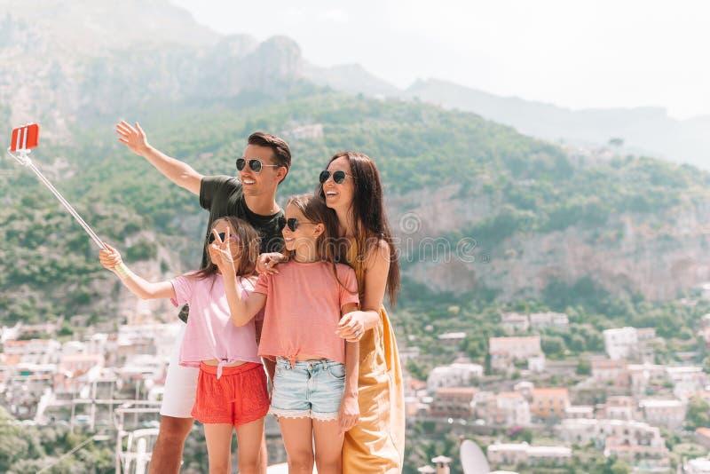 Padres y niños que toman la ciudad de Positano del fondo de la foto del selfie en Itali en la costa de Amalfi imagenes de archivo