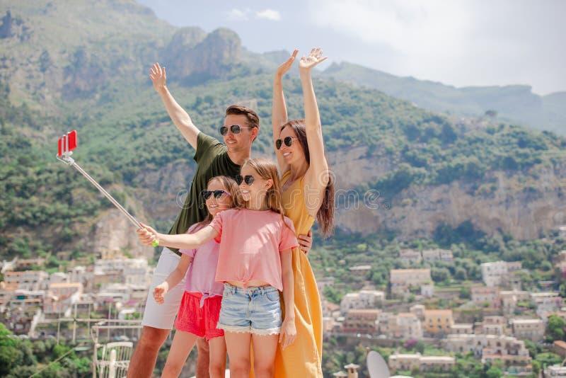 Padres y niños que toman la ciudad de Positano del fondo de la foto del selfie en Itali en la costa de Amalfi foto de archivo