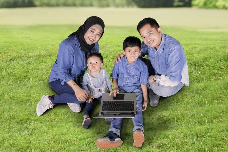 Padres y niños que usan un ordenador portátil en el parque imágenes de archivo libres de regalías