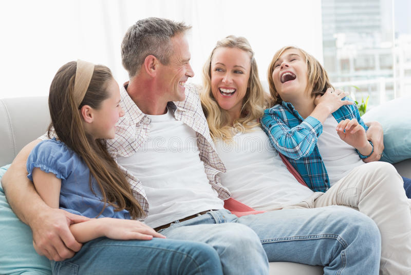 Padres y niños sonrientes que se sientan junto en el sofá foto de archivo libre de regalías