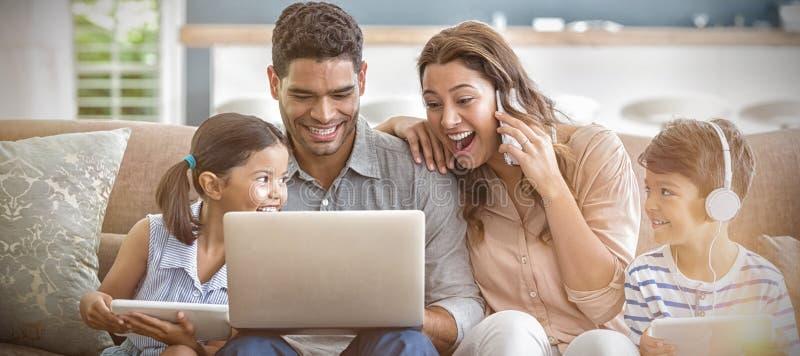 Padres y niños usando el ordenador portátil y la tableta digital en sala de estar imagenes de archivo