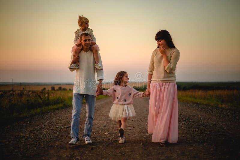 Padres y ni?os al aire libre en la puesta del sol foto de archivo
