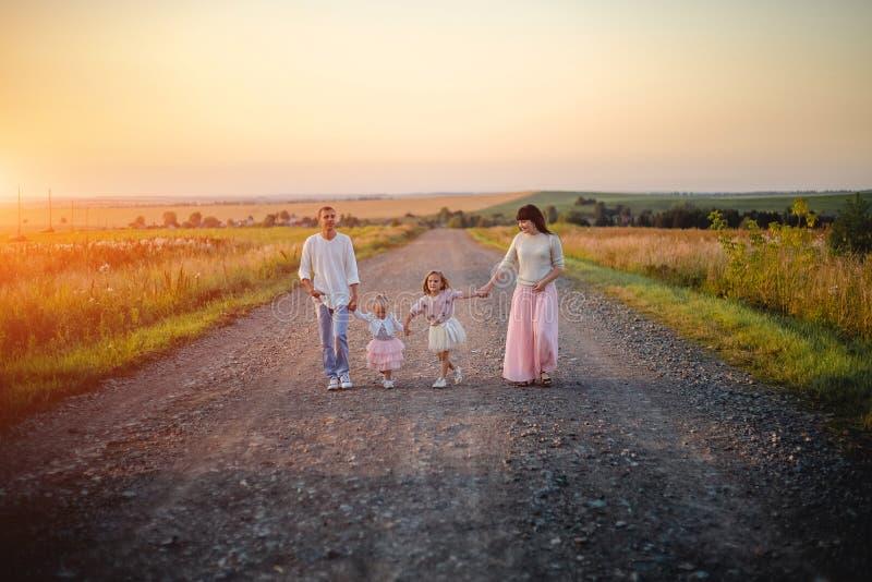 Padres y ni?os al aire libre en la puesta del sol imágenes de archivo libres de regalías