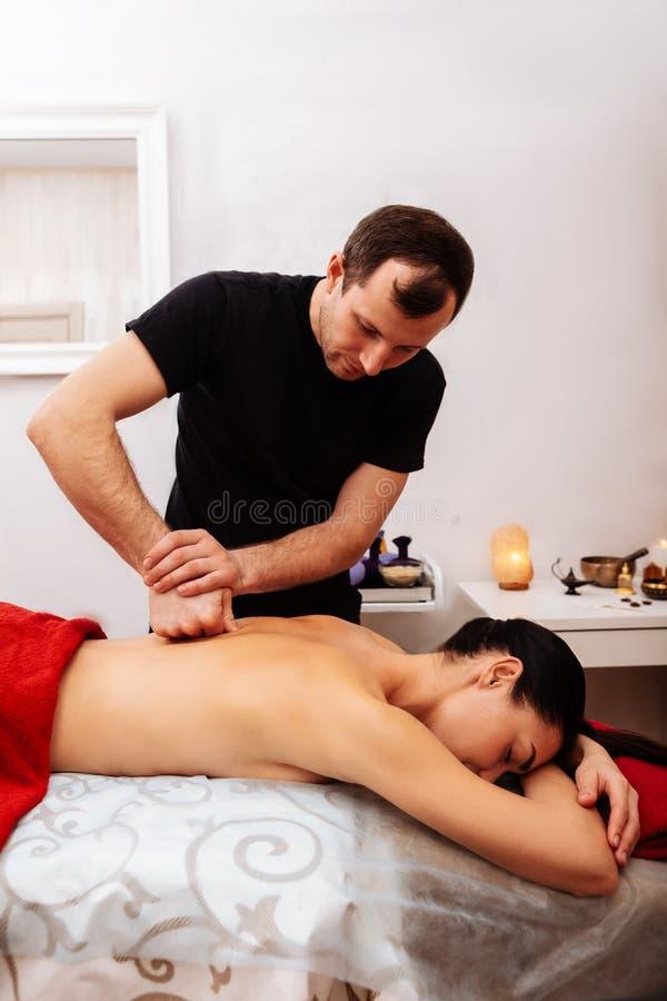 Padrone dai capelli corti in maglietta nera facendo uso del suo pugno durante il massaggio immagini stock libere da diritti