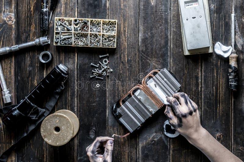 Padrone di riparazione del computer con le mani sporche scure che puliscono il pezzo elettronico sulla tavola f immagine stock libera da diritti