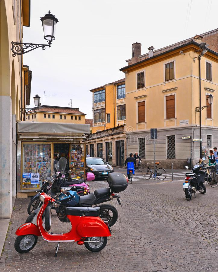 Padua Italy, 30.04.2016. Old red vintage motorcycle Vespa on the street with old buildings and people in downtown city Padova, Ven stock photo