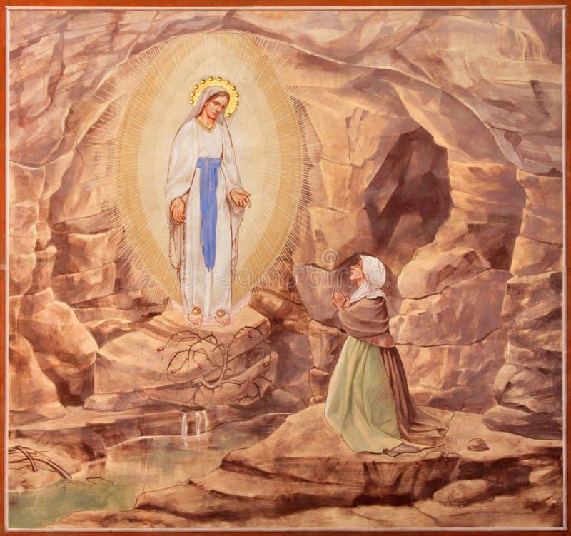 Padua - målarfärgen av Apparitioinen av jungfruliga Mary i Lourdes i kyrkliga Basilika del Carmine fotografering för bildbyråer