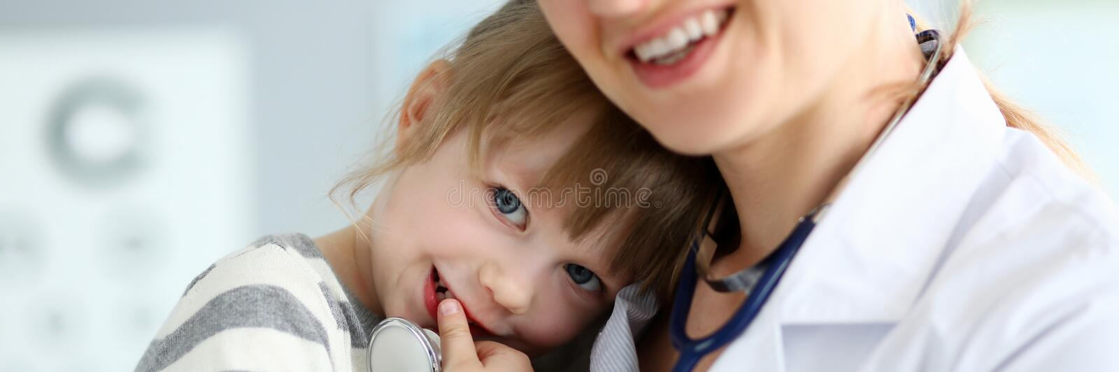 Paediatric doctor holding and hugging little cute girl patient royalty free stock photography