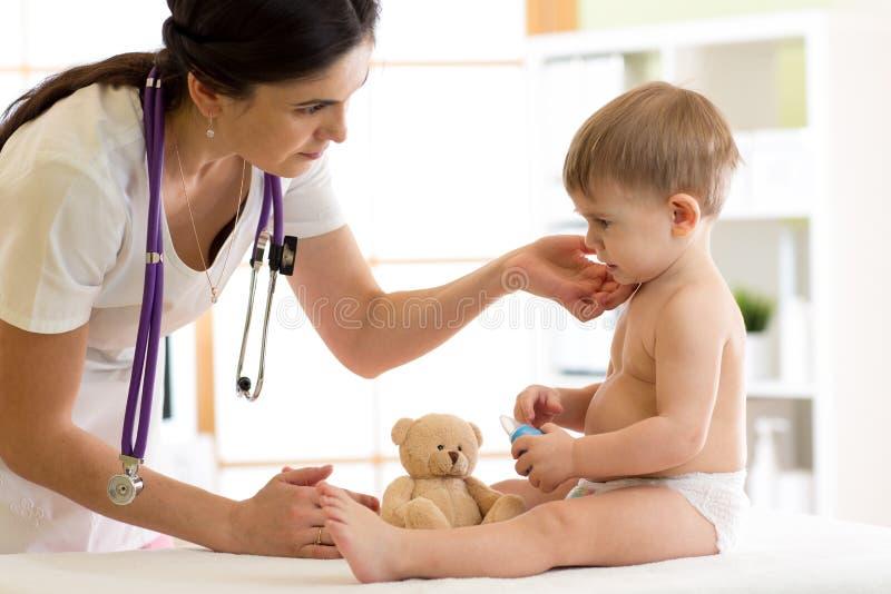 Paediatrician do doutor que verifica o pescoço do ` s do menino foto de stock royalty free