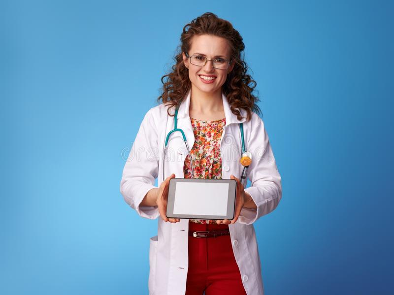 Paediatrician doctor showing tablet PC blank screen on blue royalty free stock photo
