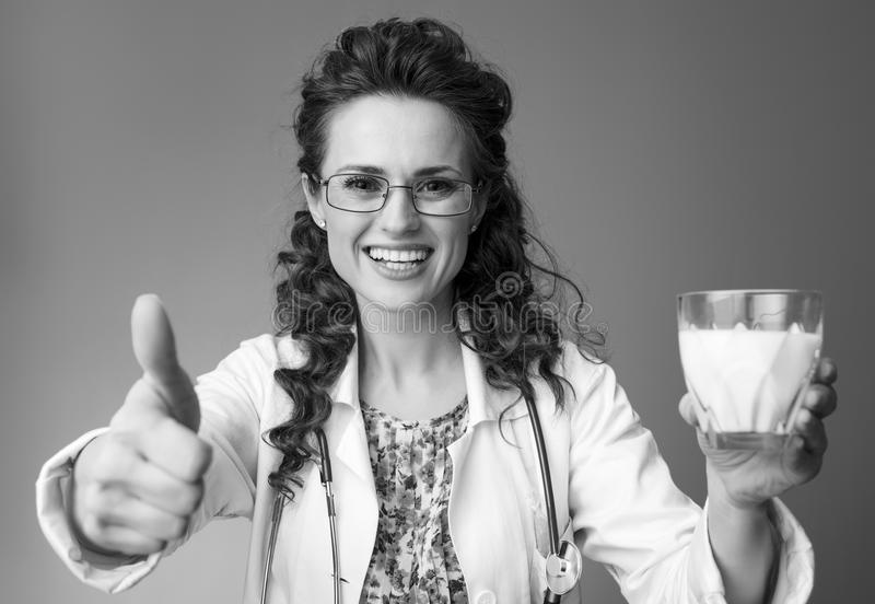 Paediatrist doctor showing thumbs up and giving a glass of milk royalty free stock images