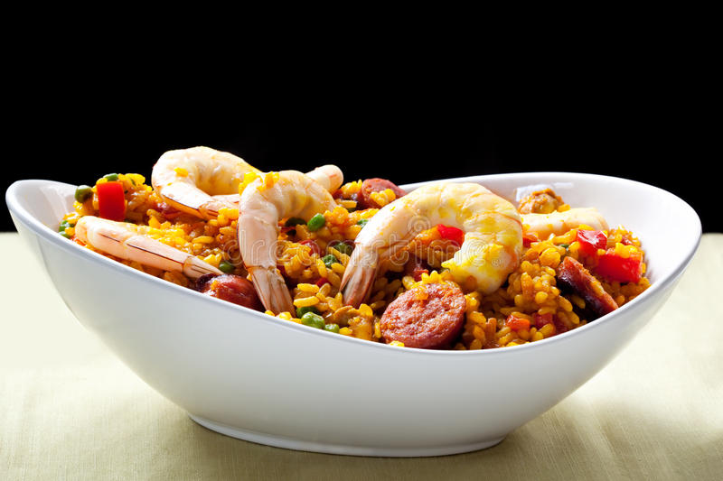 Paella. With prawns, chorizo, tomatoes, peppers and peas, in a white serving bowl royalty free stock photos