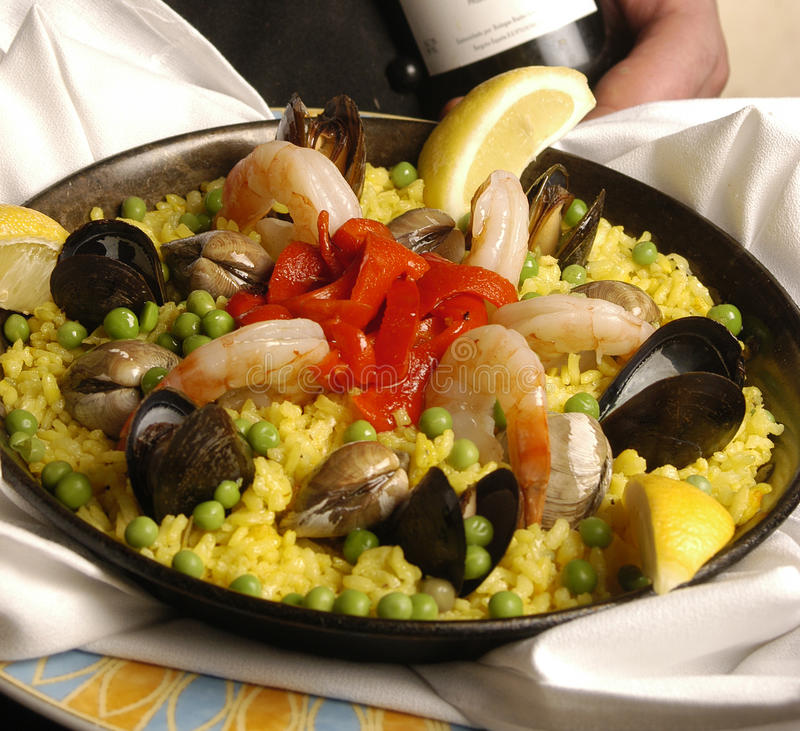 Paella. A waiter holds out paella in a pan royalty free stock photos