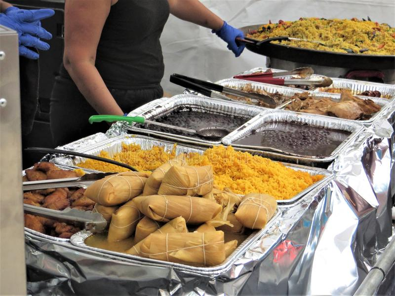 Cuban food served at Ybor City street festival. Paella, black beans, yellow ride, corn tamales, plantains, chicken and other traditional Latin food served at stock image