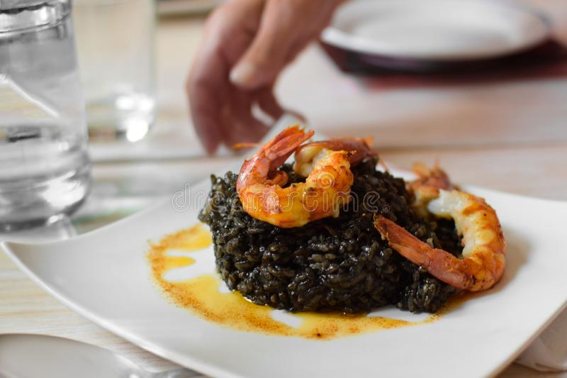 Paella from black rice with seafood shrimp on a white plate on the table stock photos
