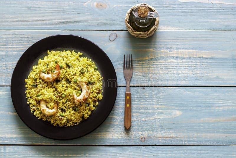 Paella con gamberetto su un fondo di legno blu fotografia stock libera da diritti