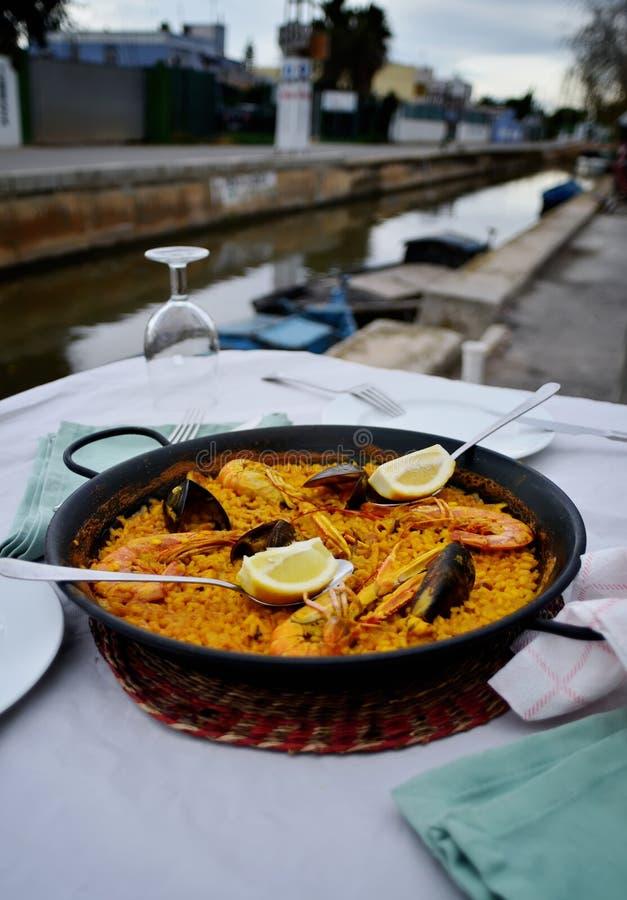 Paella de fruits de mer avec le verre de vin en café de bord de la mer, Espagne images libres de droits