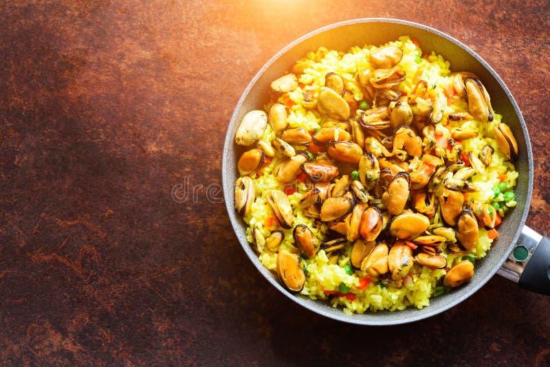 Paella espagnole traditionnelle de fruits de mer en riz de casserole, pois, crevettes, moules, calmar sur le fond foncé rustique  images stock