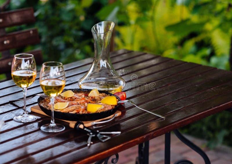 Paella i pannan med vinet på tabellen royaltyfri foto