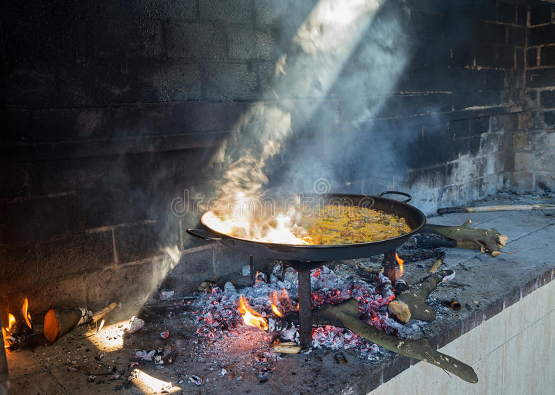 Paella and light. Preparing large dish of paella with firewood stock photography