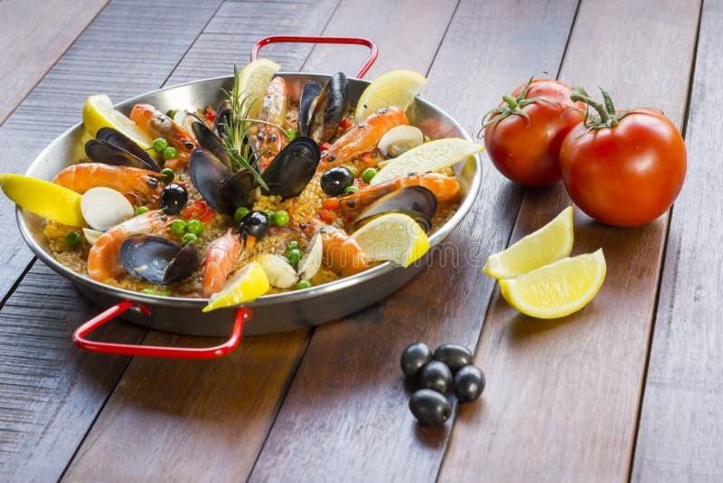 Paella mit Meeresfrüchtegemüse und -safran diente in der traditionellen Wanne stockfotos