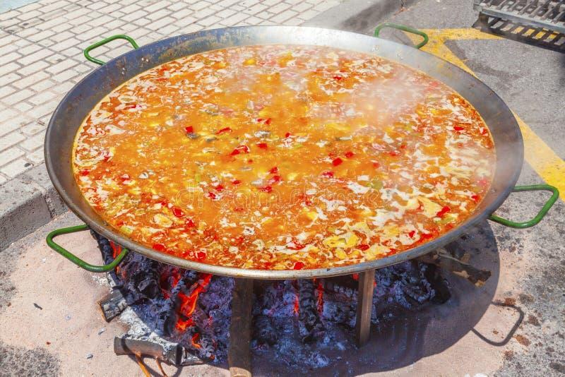 Paella od kurczaka, warzyw i ryż, Krajowy Hiszpański naczynie paella w wielkiej rynience gotuje na otwierał ogień, przy zdjęcie stock
