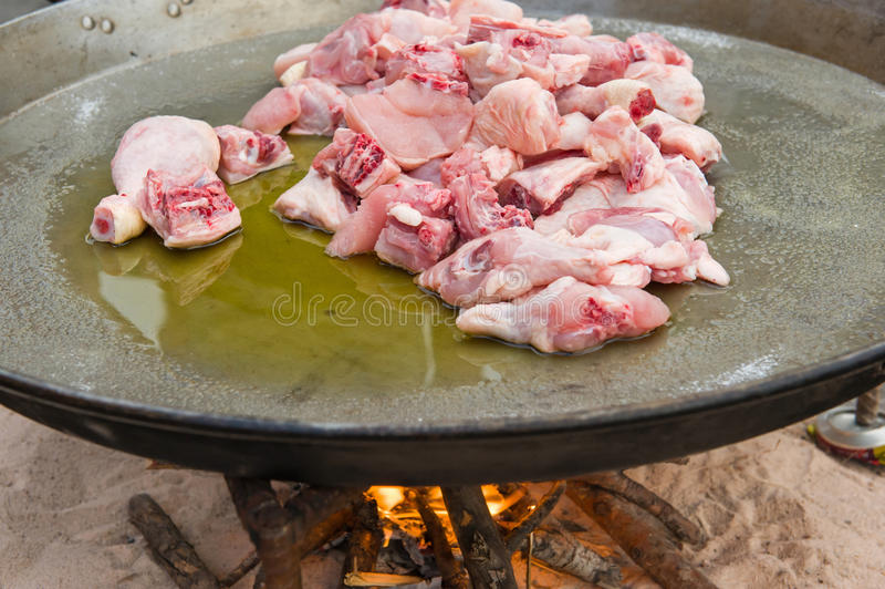 Paella preparing. Huge frying pan with chicken pieces. Traditional spanish paella preparing royalty free stock image