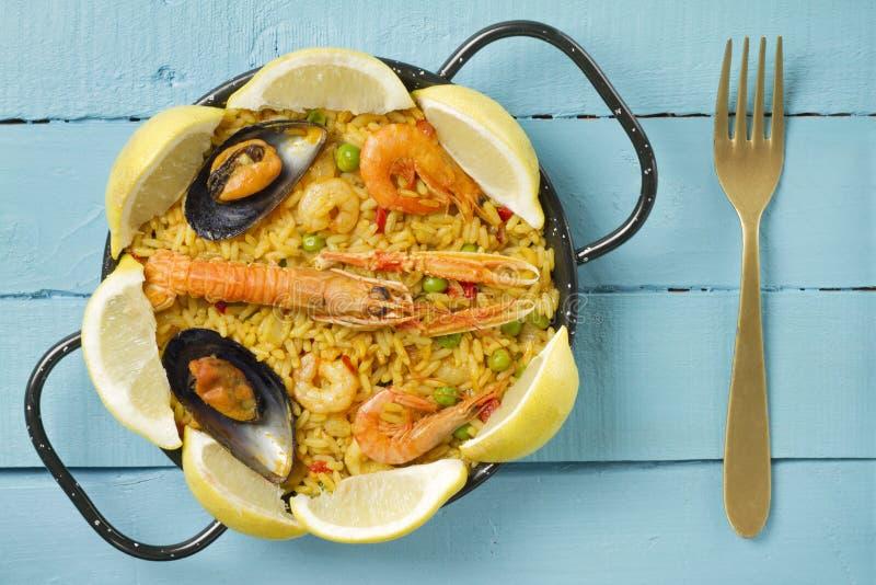 Paella spagnola su una tavola di legno blu fotografie stock