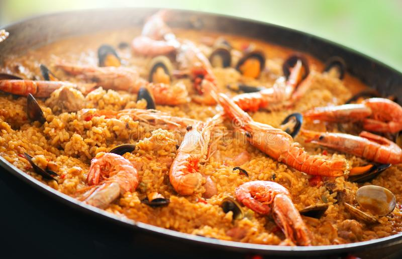 Paella. Traditional spanish food, seafood paella in the fry pan with mussels, king prawns, langoustine and squids. Cooking paella royalty free stock images