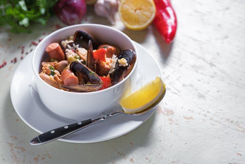 Paella w bielu talerzu z szafranowymi ryż, grochy, garnele, mussels, kałamarnica, mięso Owoce morza paella, tradycyjny hiszpański zdjęcie royalty free
