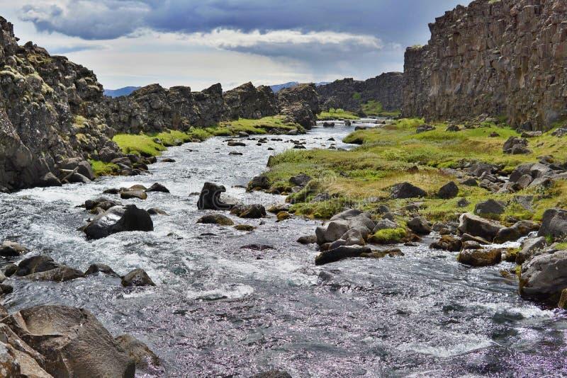 Paesaggio ad alto contrasto fatto dell'insenatura della montagna fra le colline scure nel parco nazionale di Thingvellir immagine stock libera da diritti