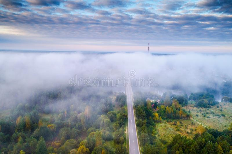 Paesaggio aereo di alba di mattina di foschia sopra la foresta e la strada fotografie stock