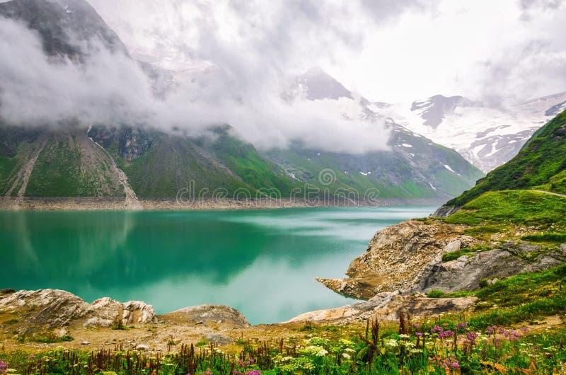 Paesaggio alpino con il lago della montagna al giorno nuvoloso immagine stock libera da diritti