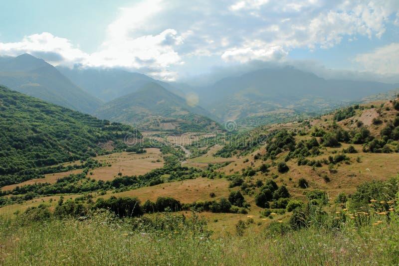 Paesaggio in Armenia con le montagne e una valle con le nuvole e la spazzola verde immagini stock libere da diritti