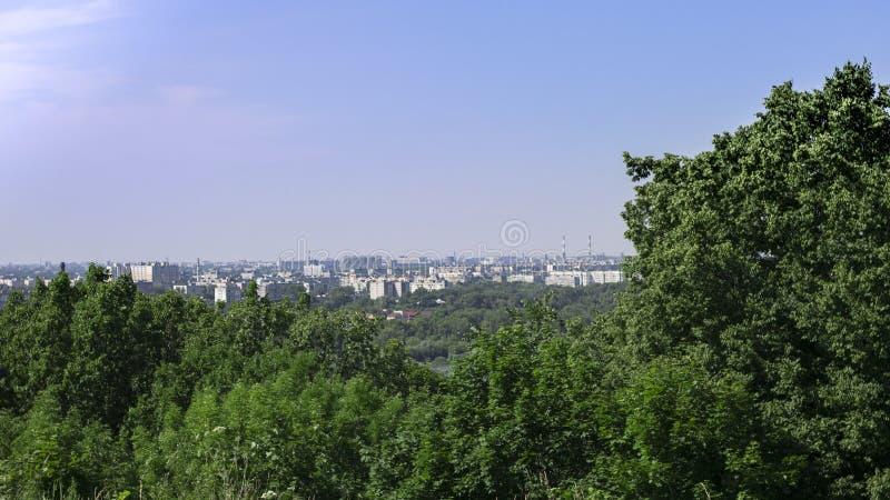 Paesaggio attraverso gli alberi potete vedere la città sulle banche del fiume fotografie stock