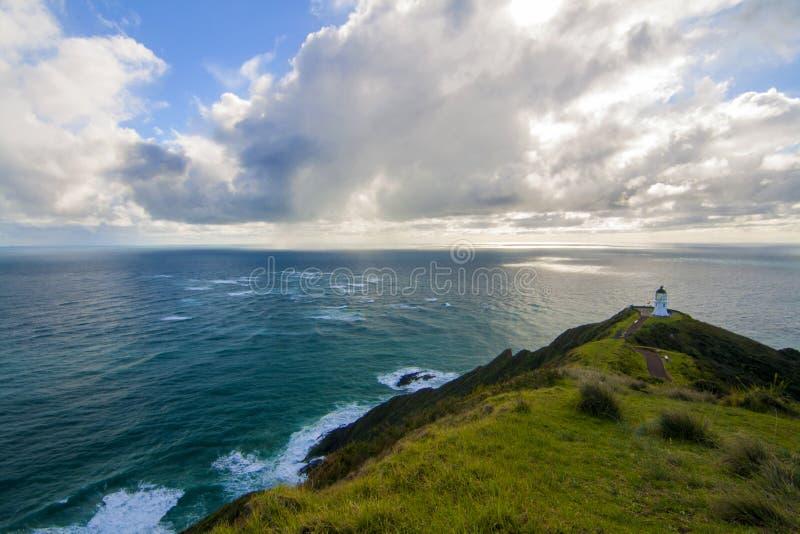 Paesaggio bello dell'oceano Pacifico con il faro sulla cima del picco della scogliera, casa leggera di Reinga del capo, Northland immagine stock libera da diritti