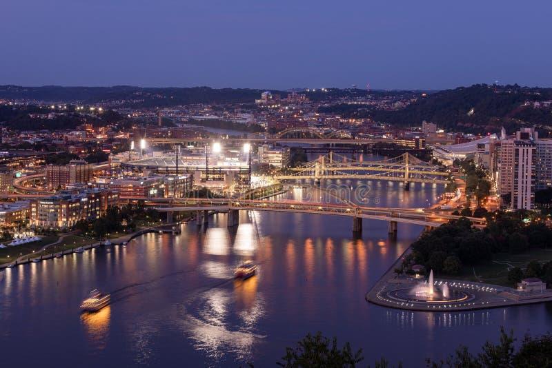 Paesaggio cittadino di Pittsburgh e luce di sera Blurry Ferries a causa di una lunga esposizione fotografia stock
