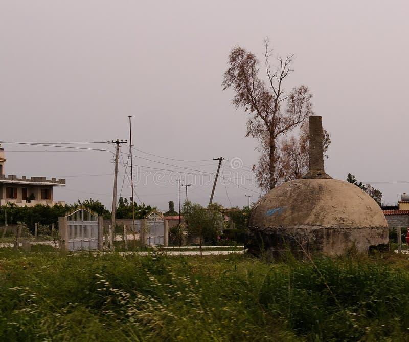 Paesaggio con i bunker militari in mezzo all'campi rurali, Apollonia, Fier, Albania fotografie stock libere da diritti