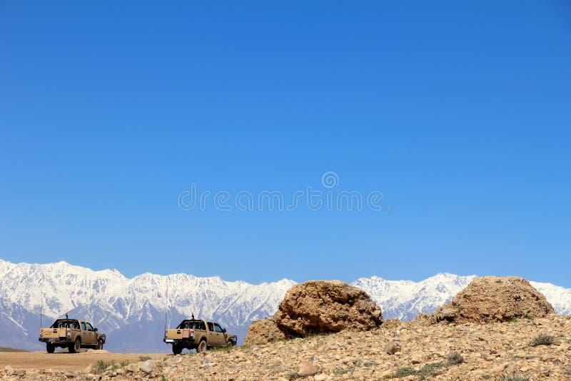 Paesaggio con i veicoli militari e le montagne fotografia stock libera da diritti