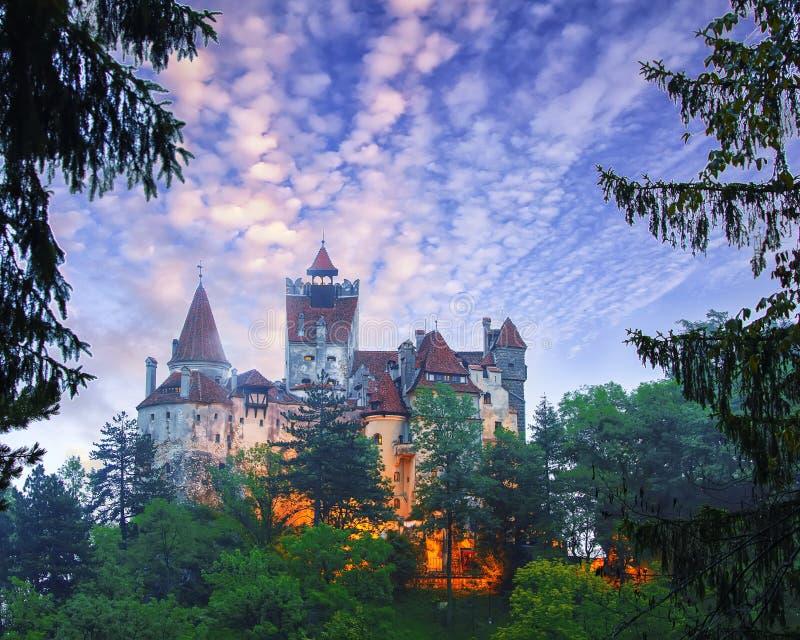 Paesaggio con il castello medievale della crusca conosciuto per il mito di Dracula al tramonto fotografia stock