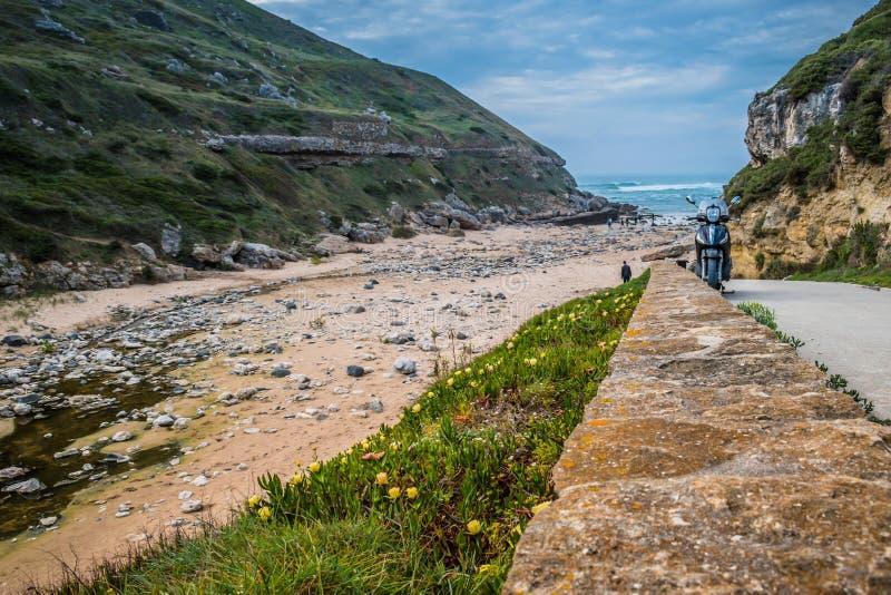 Paesaggio con il motociclo accanto alla spiaggia di Samarra, siluette della gente nella sabbia con le rocce, Sintra - Lisbona, Po fotografia stock libera da diritti
