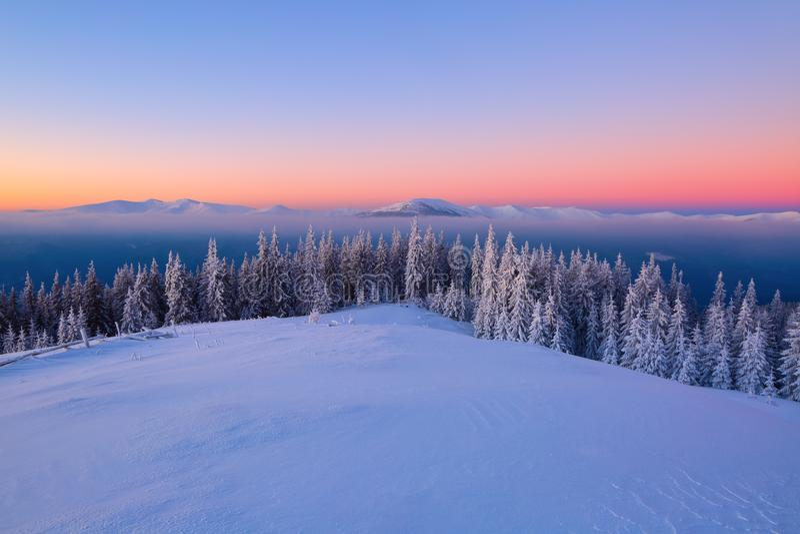 Paesaggio con le alte montagne coperte di neve Struttura congelata interessante Bella alba di inverno con cielo blu arancio fotografia stock