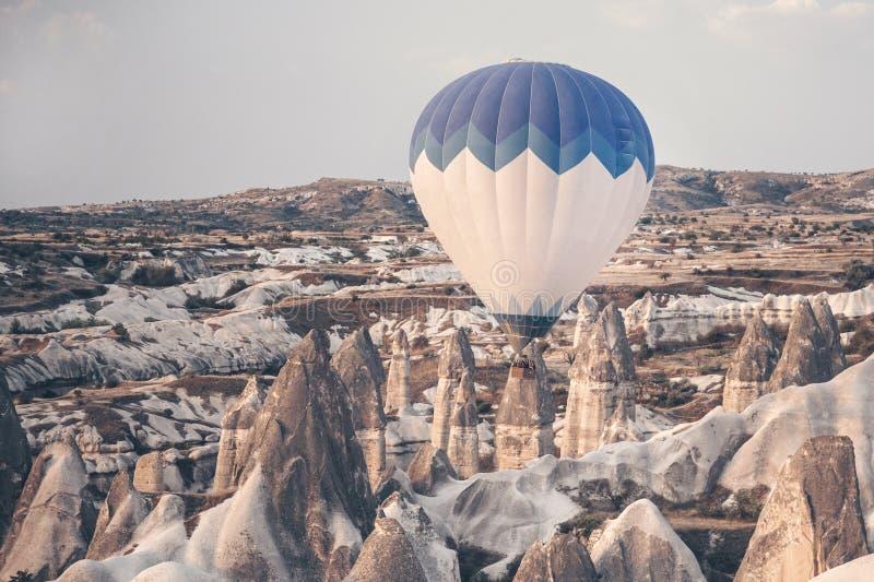 Paesaggio con palloncino ad aria calda che vola bassa sopra le montagne La famosa regione turca Cappadocia con montagne e fotografie stock libere da diritti