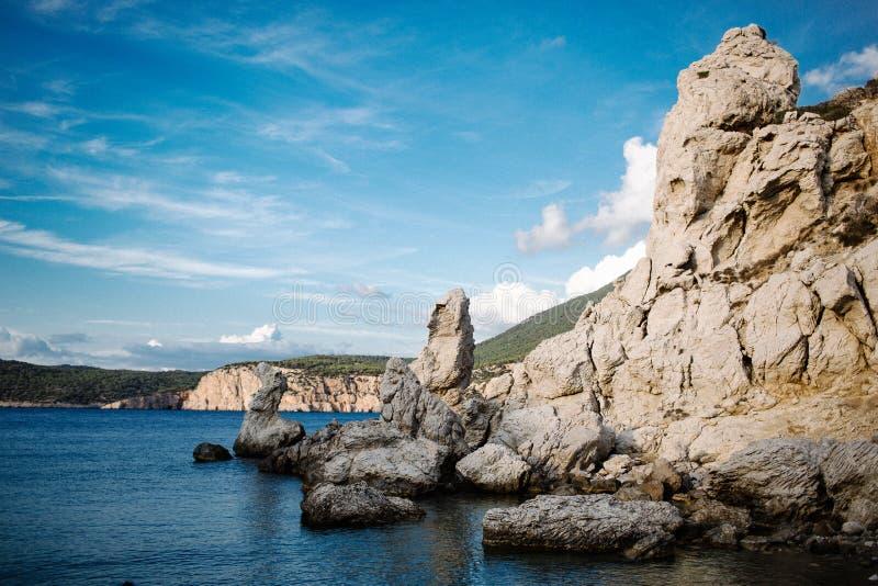 Paesaggio con una bella baia, una spiaggia in pietra e una chiara acqua blu Barca sulla baia sull'isola di Rhodes fotografie stock libere da diritti