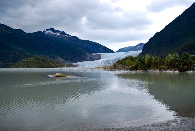 Paesaggio d'Alasca con il ghiacciaio di fusione nella valle fra due montagne fotografia stock