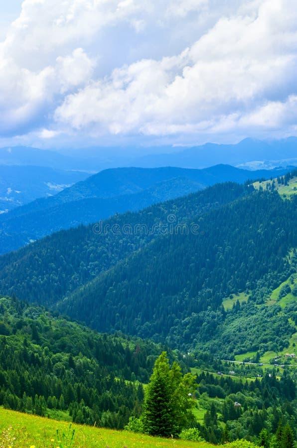 Paesaggio da altezza ai pendii di montagna, distanza blu, prato fotografia stock