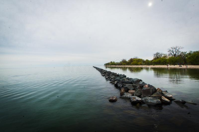 Paesaggio del bordo dell'acqua con roccia che allunga nella distanza fotografie stock