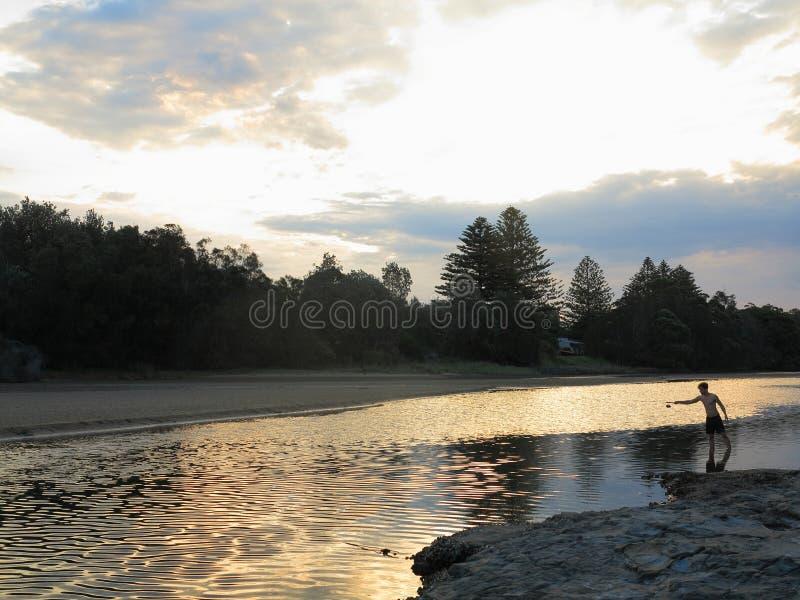 Paesaggio del fiume con pesca del giovane dal crepuscolo immagini stock libere da diritti