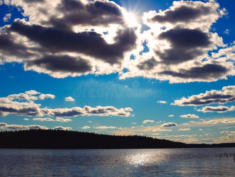 Paesaggio del lago con le nuvole e Sunbeam fotografia stock