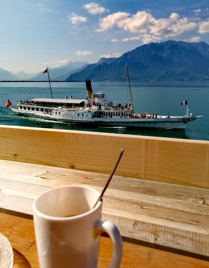 Paesaggio del lago Lemano e le ammaccature du Midi con una barca fotografie stock libere da diritti